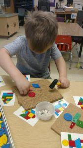 student playing with pattern blocks