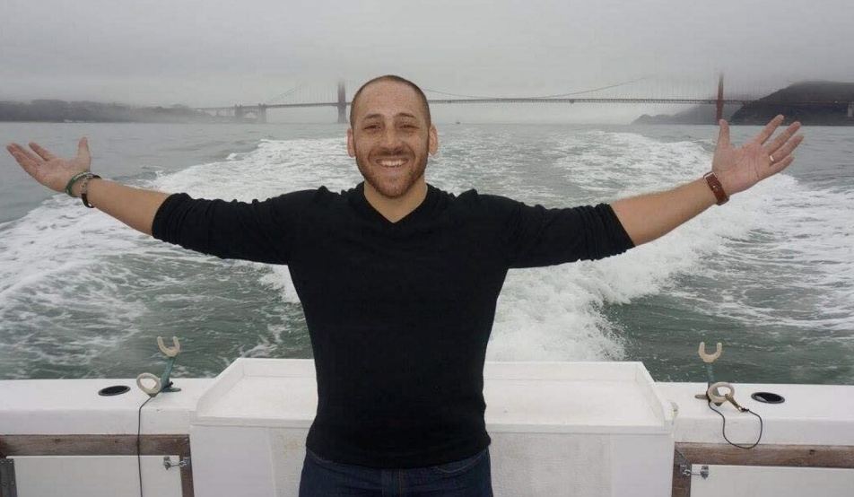Kevin Hines stands with arms outstretched with the Golden Gate Bridge behind him