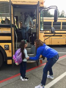 School counselor talks to girl at bus